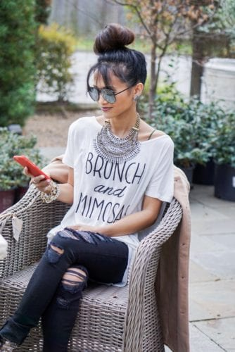 bib necklace, top bun, quay desi sunglasses, black ripped jeans