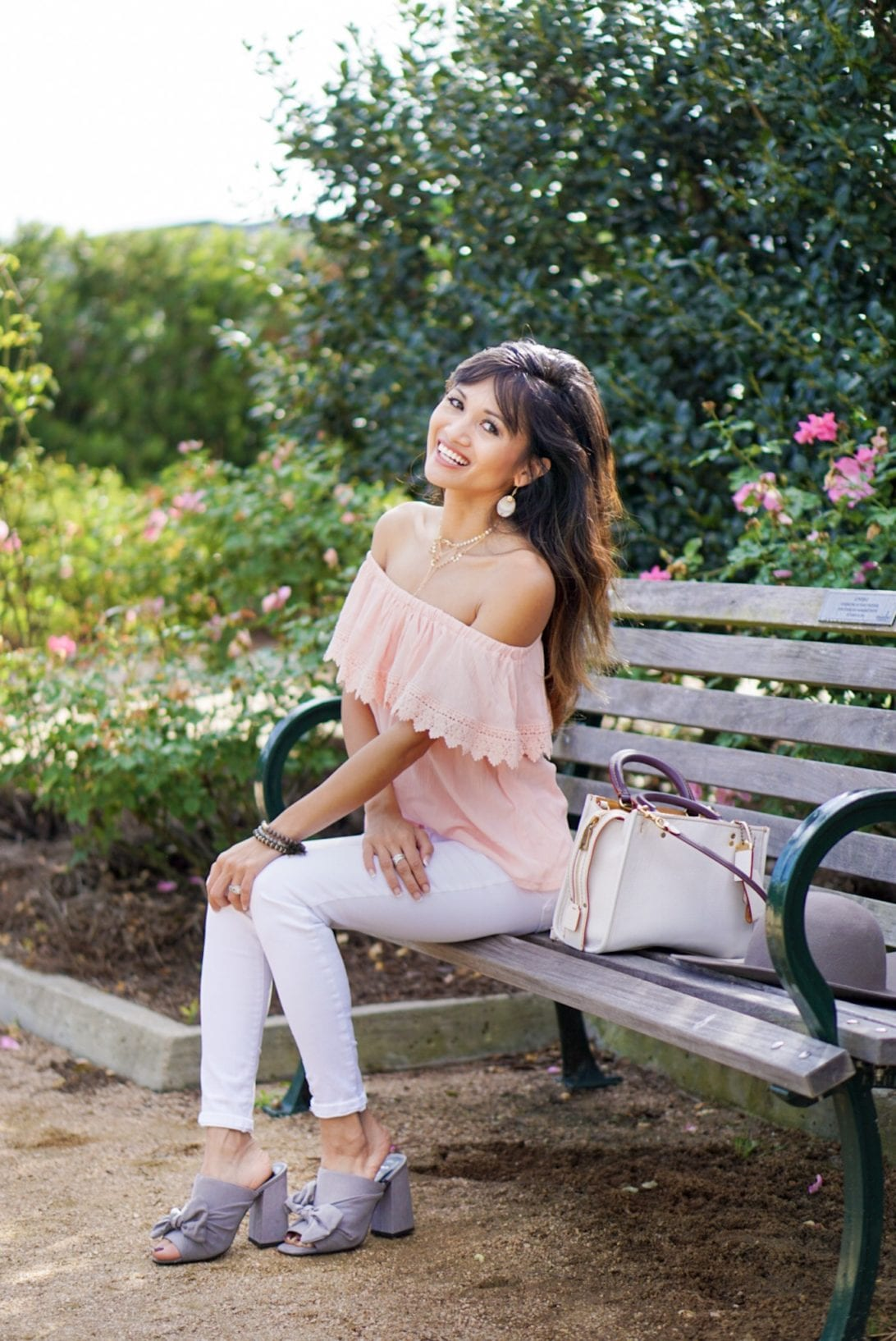 peach off the shoulder top, white jeans, coach rogue bag, gray mules, rose garden