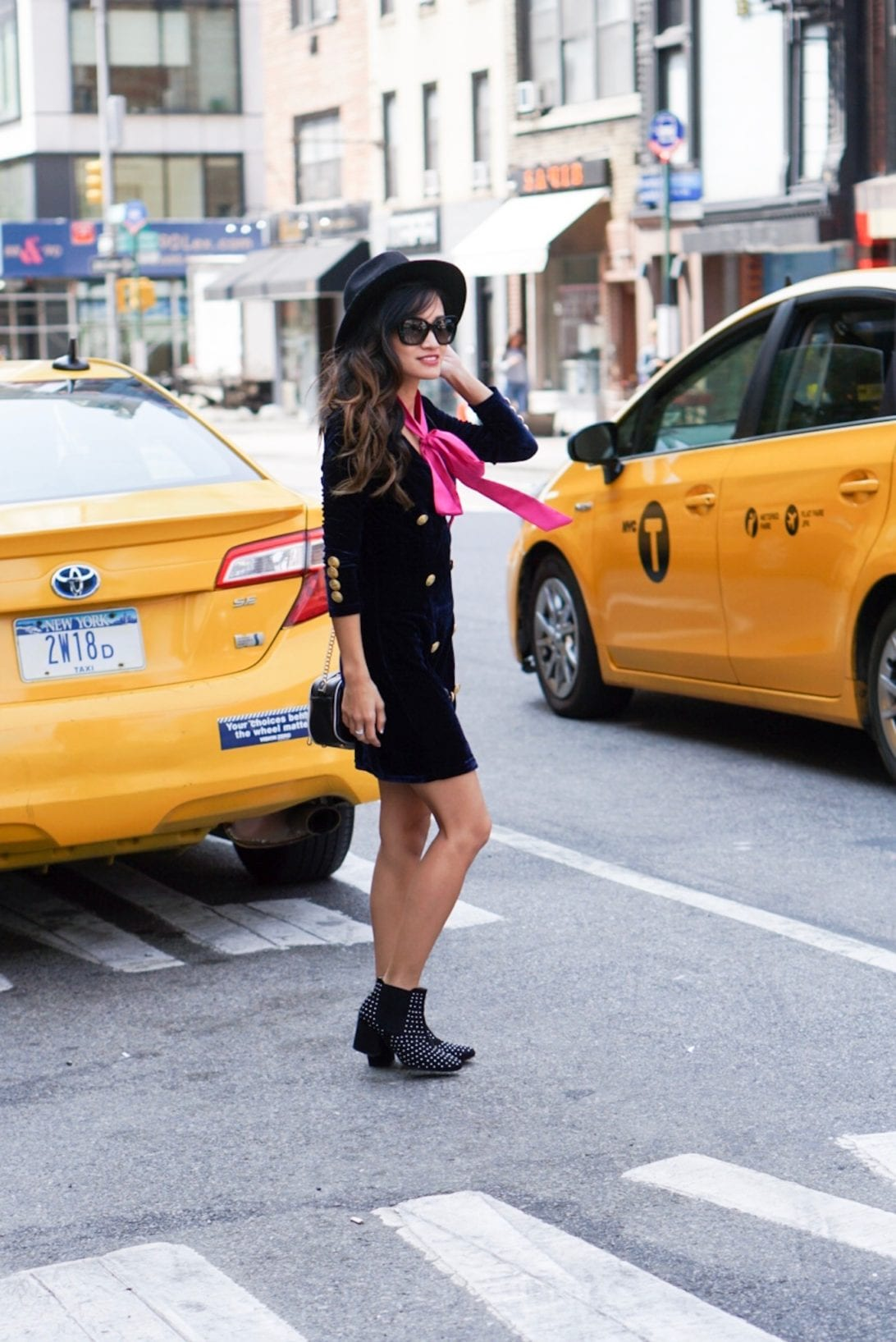 NYFW, NYFW STYLE, New York FASHION WEEK, NYC STREET STYLE, NYC CAB SHOT, PINK BOW TIE, STUDDED BOOTS, BLACK FEDORA, MILITARY DRESS, CAMERA BAG, VELVET DRESS, VERSACE SUNGLASSES