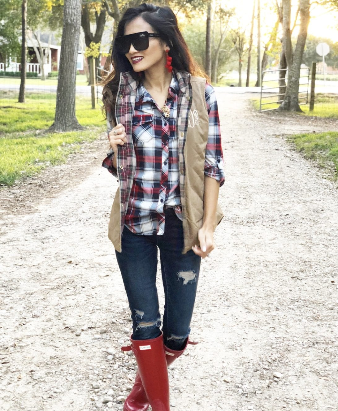 hunter boots, hunter boots outfit, holiday outfits, how to wear hunter boots, christmas outfits with hunter boots, gift guide for her, red hunter boots, hunter boots for the holidays, monogrammed vest, quay cafe racer, red bauble bar earrings, blank NYC jeans, red plaid shirt