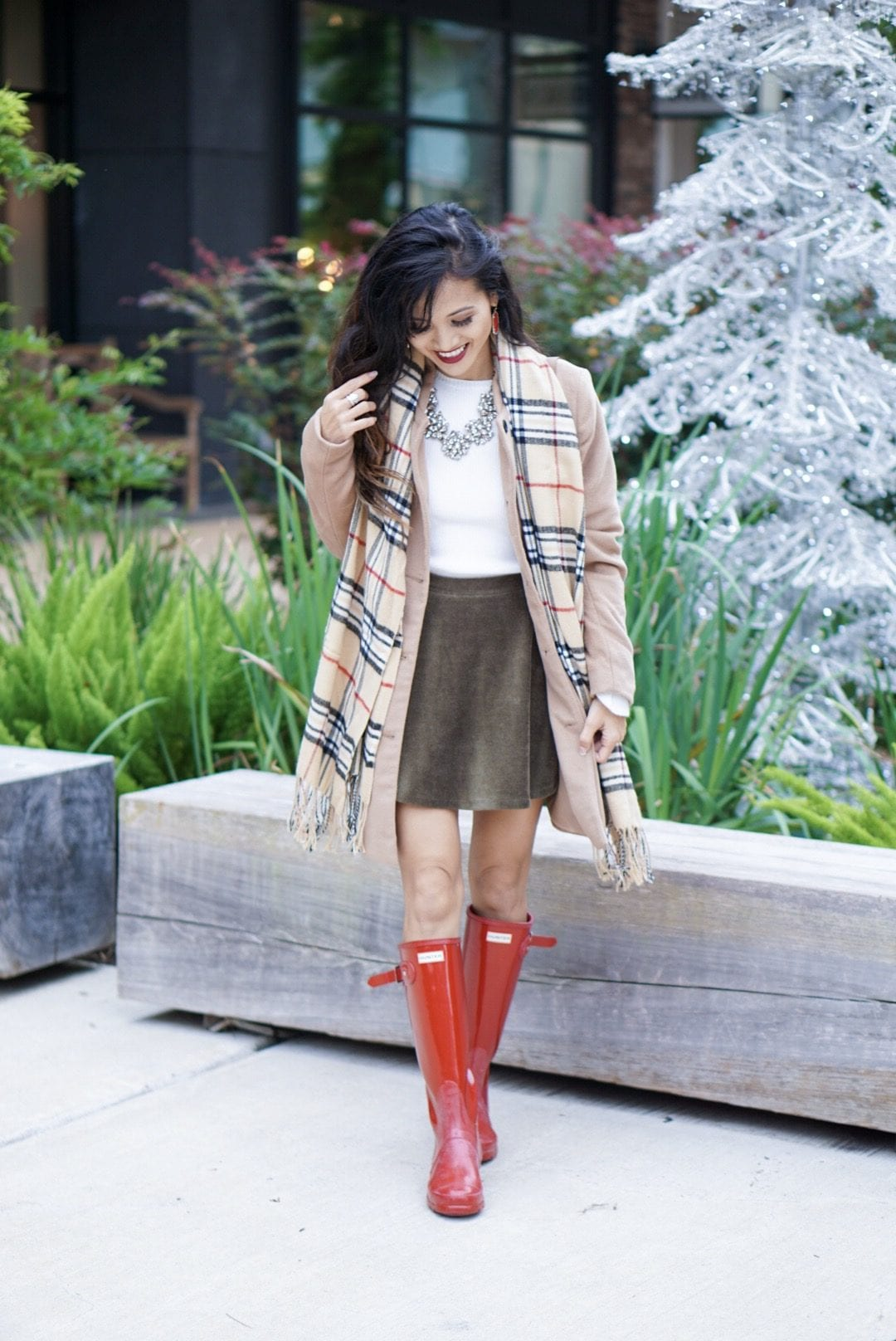 hunter boots, hunter boots outfit, holiday outfits, how to wear hunter boots, christmas outfits with hunter boots, gift guide for her, red hunter boots, hunter boots for the holidays, plaid scarf, monogrammed scarf, camel coat, corduroy skirt, bauble bar necklace