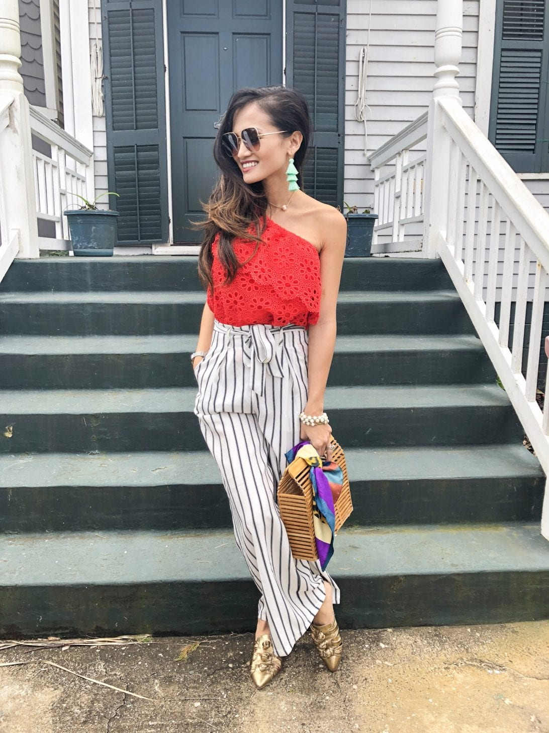 Jack by BB Dakota Lolita Top, striped pants, wide leg culottes, bamboo bag, quay sunglasses, one shoulder top, eyelet top, spring style, spring outfit, spring fashion, Rebecca Minkoff slides, Rebecca Minkoff Aden Slides, accessories for spring, tassel earrings