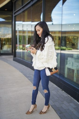 pom sweater, leopard heels, freepeople jeans, busted knee jeans