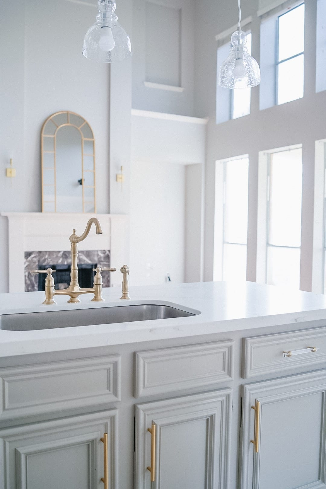 gold kitchen faucet, open to family room, flat countertop, anew grey cabinets, clear and gold cabinet pulls