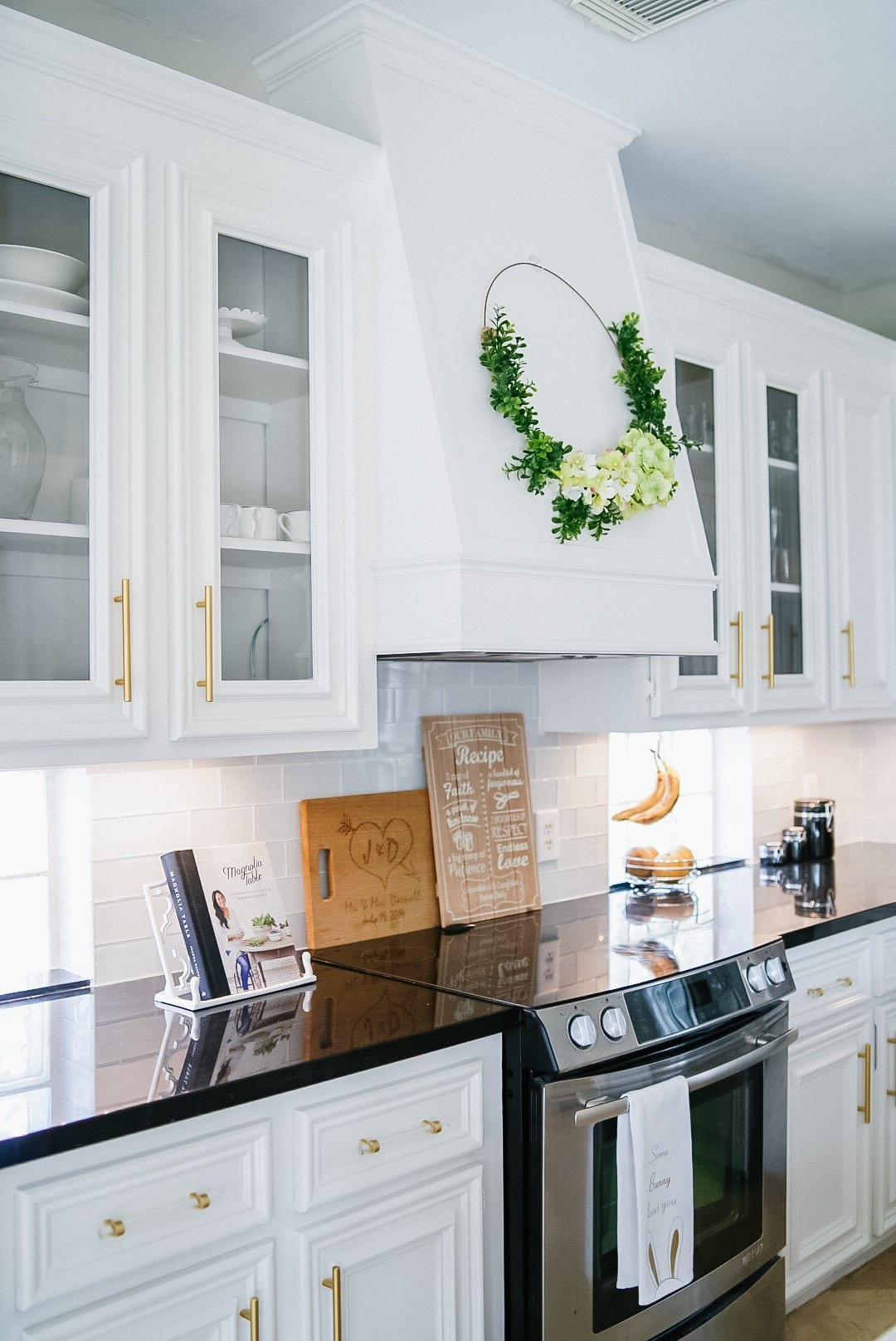 absolute black quartz countertop, white cabinets, glass doors, Magnolia cookbook, electric stovetop, white custom vent hood
