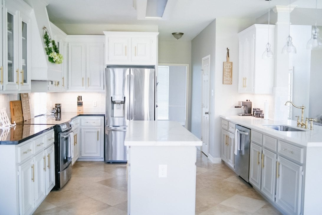 gold and white kitchen, kitchen island, subway tiles, contrasting countertops and cabinets
