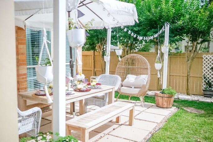 outdoor patio, patio diy, patio makeover, egg chair, whiskey barrel planters, whiskey barrel lantern post, string lights